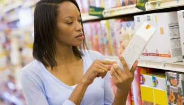 Shopper checking food labelling in supermarket