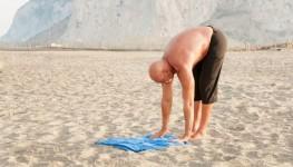 Older Man stretching on beach 1800x1200_Dollarphotoclub_46689970