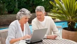 Older couple working their internet business in garden Dollarphotoclub_