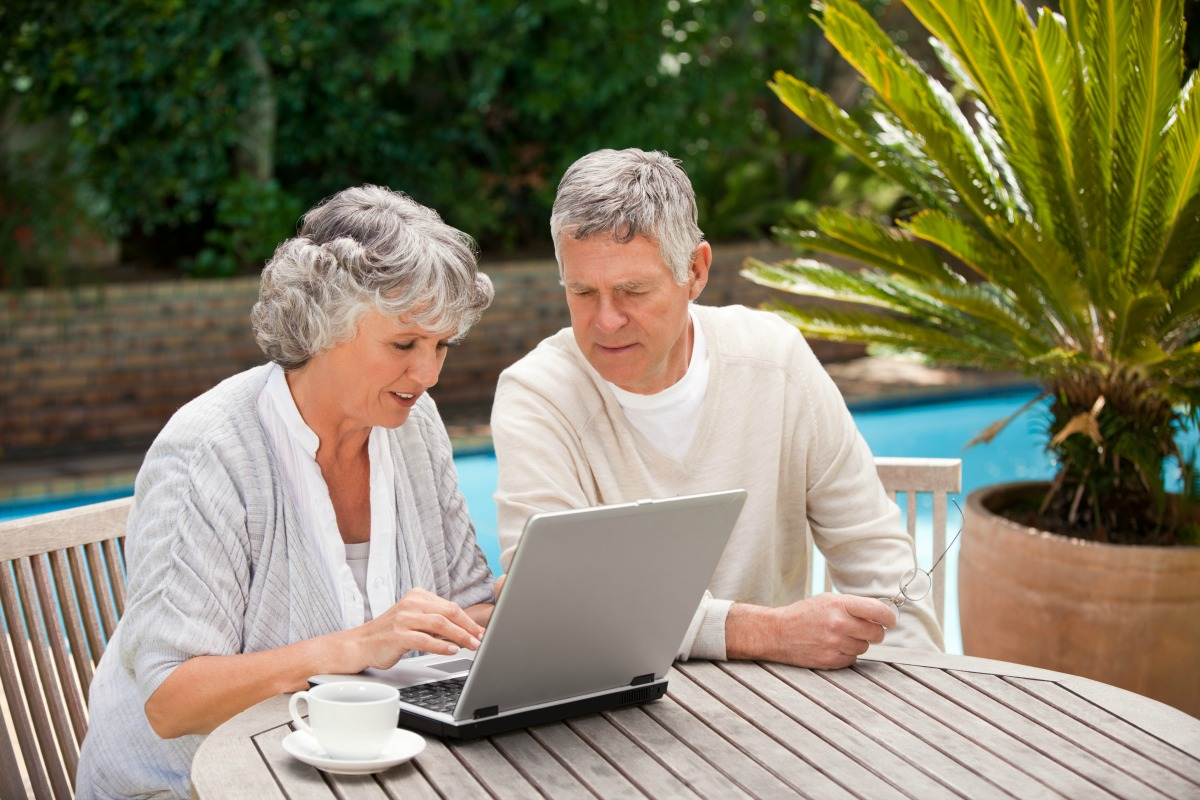 Older couple working their internet business in garden Dollarphotoclub_